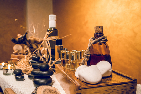 Spa essential aromatic oil in vintage bottle and massage basalt zen stones and candles on the table