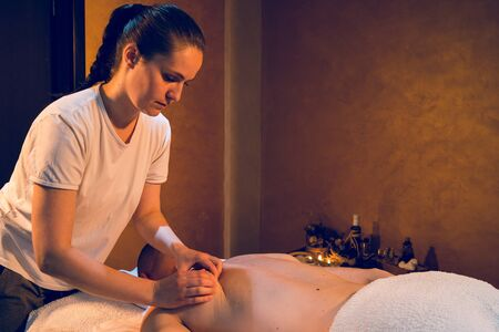 Young woman giving relaxing sport massage to the client at spa