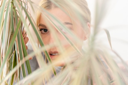 Portrait of beautiful young woman with blonde hair trough the leaves of the plant in nature home