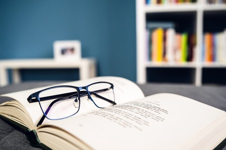 Reading glasses and stack of books reading and learning concept at home school study