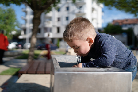Little boy at the public fountain playing with water drinking in summer sunny day thirsty refreshment