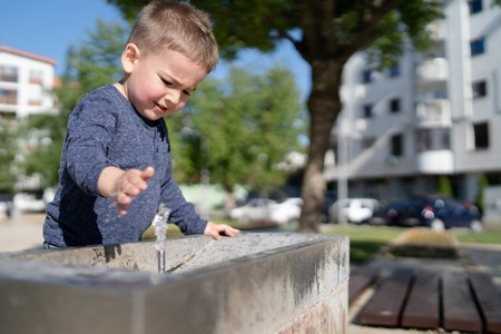 Little boy at the public fountain playing with water drinking in summer sunny day