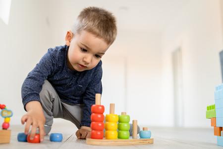 Petit garçon jouant avec des jouets de casse-tête en bois sur le plancher en bois à la maison