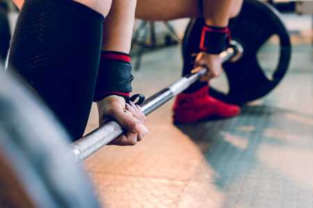 Close up on woman female athlete holding grip on the barbell at the gym ready for dead lift training work out bodybuilding strong power lifting