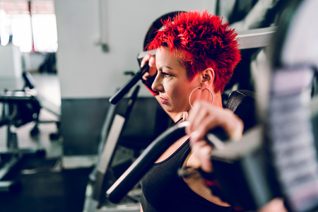 Young beautiful woman with short red hair at the gym by the shoulder press machine resting at workout bodybuilding fitness training 免版税图像