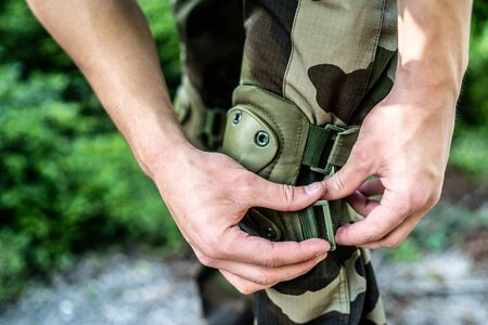 Special police military soldier putting knee protection pads for the mission action combat intervention