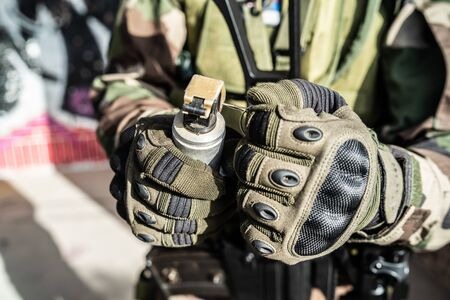 Close up on SWAT special military police force holding shock grenade ready to activate in combat action anti Terrorist intervention