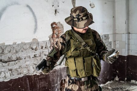 Military soldier dogs of war crime terrorist in the ruined building holding gun and hand grenade Stock Photo