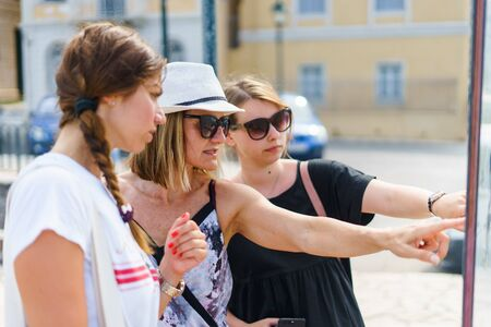 Three female tourist women looking at the map location on the info panel in the Corfu Town tourist destination in a summer day on the vacation holiday Standard-Bild