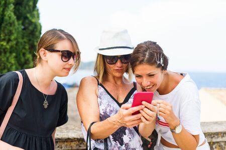 Trzy kobiety patrzące na smartfona, szukające zdjęć z informacjami turystycznymi w mieście Korfu