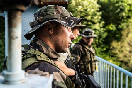young soldiers on patrol platoon on the mission combat operation waiting for instructions on the bridge near the war zone