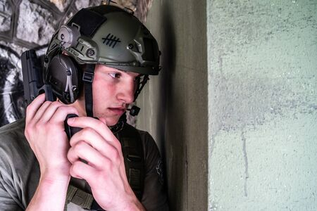 Young pilot after the catapult evacuation rescue mission aiming gun in ruined building Stock Photo