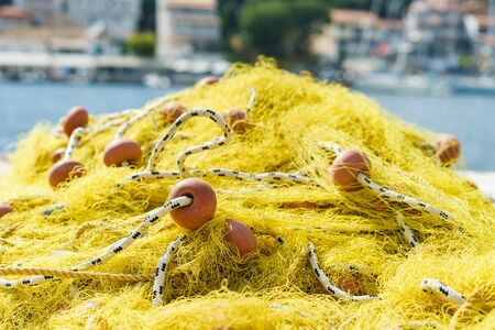 Yellow fishing net on the dock in harbor by the sea in summer day