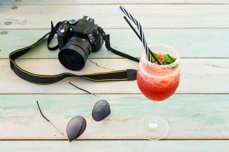 DSLR digital camera sunglasses and red fruit cocktail on the wooden table on summer day vacation holiday tourist