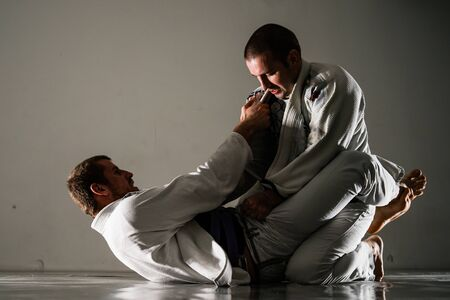 Brazilian jiu-jitsu BJJ training sparing on the tatami two fighters in guard position in training