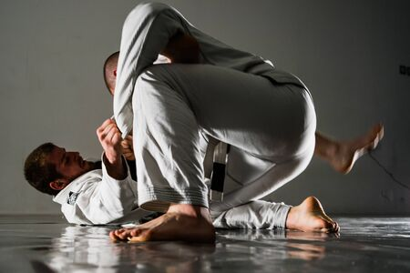Brazilian jiu-jitsu BJJ training sparing on the tatami two fighters in guard position in training Stock Photo
