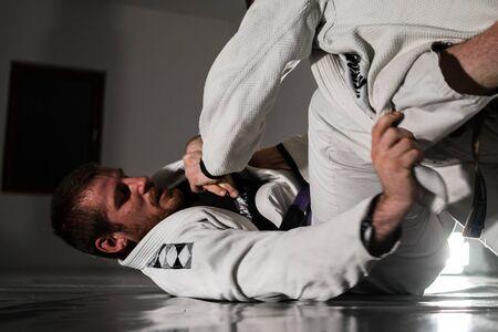 Jiu jitsu brésilien BJJ épargnant dans la formation de deux athlètes combattants d'arts martiaux portant des kimonos gi s'entraînant pour combattre la garde de revers