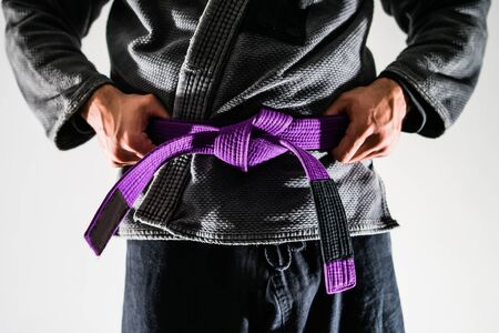 Close Up On Brazilian Jiu JItsu BJJ Fighter in a Gi Kimono Holding Purple Belt around his waist