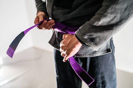 Close Up On Brazilian Jiu JItsu BJJ Fighter in a Gi Kimono Holding Purple Belt around his waist