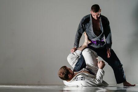 Brazilain Jiu JItsu BJJ Fighters in training sparing open x guard Фото со стока