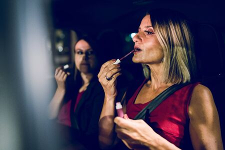 Two women mother and daughter friends putting make up repair in the car at night getting ready to go out Banco de Imagens