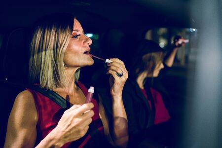 Two women mother and daughter friends putting make up repair lipstick in the car at night getting ready to go out