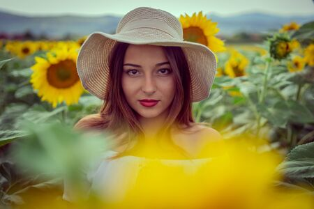 Portrait of young woman in white dress standing in the crops field of sunflowers in a sunny summer day wearing hat