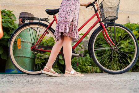 Close up on womans legs female standing beside the bicycle wearing summer dress in a sunny day
