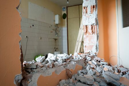 Wall smashed into debris room in apartment ready for renovation with destroyed smashed wall demolish