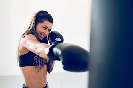 Young woman training boxing punching heavy bag with gloves on her hands at the gym martial arts academy