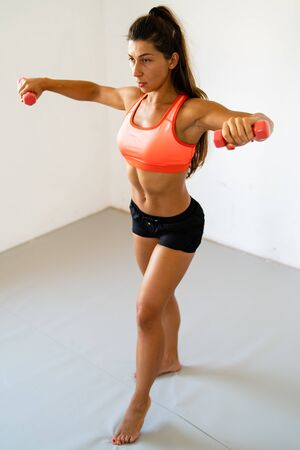 Side view Midsection of sporty fit sportswoman doing shoulder exercise with dumbbells at the training workout aerobic pose muscular