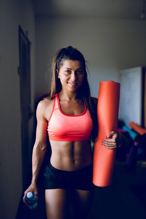 Muscular sporty fit sportswoman holding bottle of water and yoga mat by the window at the gym studio going to the training workout