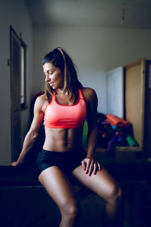 Midsection of young muscular fit fitness woman sporty sportswoman sitting on the bench at the gym posing her muscles body Фото со стока