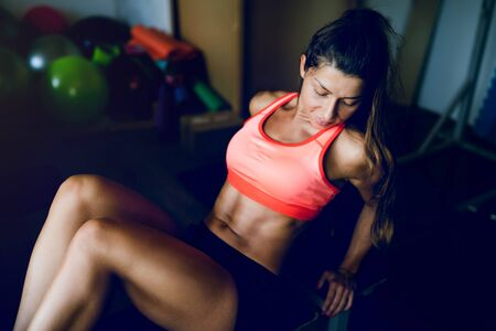 Midsection of young muscular fit fitness woman sporty sportswoman sitting on the bench at the gym posing her muscles body curl Reklamní fotografie