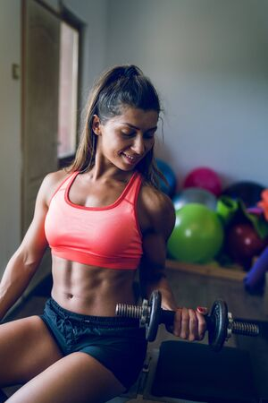 Midsection of young muscular fit fitness woman sporty sportswoman sitting on the bench at the gym posing her muscles body with dumbbell biceps curl