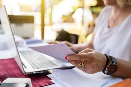 Freelancer woman working on her laptop entering data from document typing while sitting by the table at terrace checking paperwork from the account database invoice loan