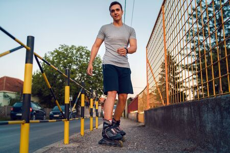 Young man on roller blades skates riding by the fence wall looking waiting in a summer day evening rollerblading