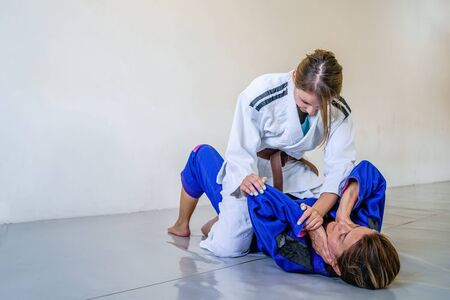 Two brazilian jiu jitsu BJJ women female athletes fighting in training sparring mount position americana attacking judo kimono gi ne waza