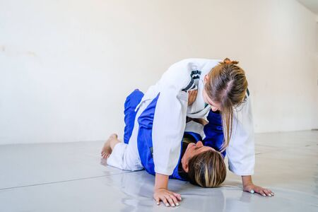 Two brazilian jiu jitsu BJJ women female athletes fighting in training sparring mount position attacking self defense judo kimono gi