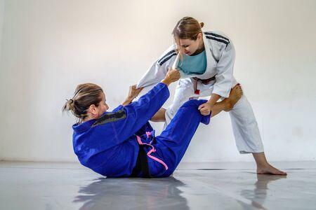 De la Riva Guard im brasilianischen Jiu Jitsu Bjj Training Sparring zwei weibliche Sportlerinnen Kämpfer Bohrtechniken für den Wettbewerb Advanced Guard Schwarz-Braun-Gürtel