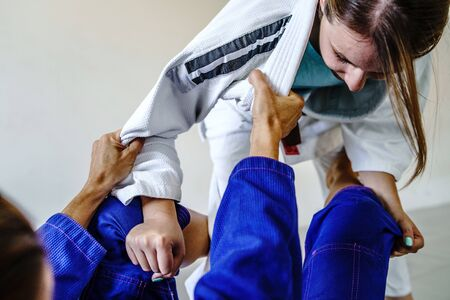 Grips from the guard in brazilian jiu jitsu bjj training sparring two female women athletes fighters drilling techniques for the competition advanced guard holding kimono gi 免版税图像