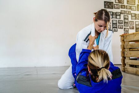 Grips from the guard in brazilian jiu jitsu bjj training sparring two female women athletes fighters drilling techniques for the competition closed guard holding kimono gi