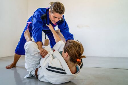 Grips from the guard in brazilian jiu jitsu bjj training sparring two female women athletes fighters drilling techniques for the competition closed guard holding kimono gi pass 免版税图像
