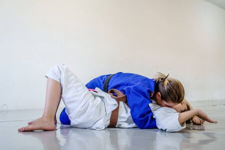 Side control 100 kilos position, americana submission judo bjj brazilian jiu-jitsu training sparring two women female fighters in training wearing kimono