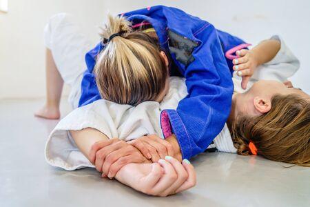 Side control 100 kilos position, americana submission judo bjj brazilian jiu-jitsu training sparring two women female fighters in training wearing kimono