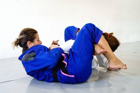 Omoplata sumisión judo bjj jiu jitsu brasileño entrenamiento sparring dos mujeres luchadoras en formación vistiendo kimono gi Foto de archivo