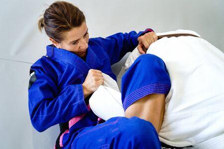 Omoplata submission judo bjj brazilian jiu jitsu training sparring two women female fighters in training wearing kimono gi Archivio Fotografico - 129135899