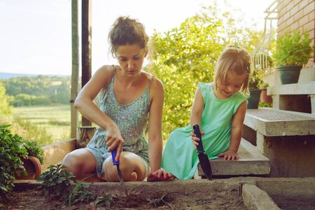 Young mother and daughter digging picking ground dirt land in their yard garden near the home house family planting flowers or seeds using gardening tools in summer day