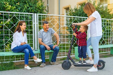 Young woman riding electric kick scooter with her little boy son while talking to grandfather senior man and woman sitting on the bench in summer day 写真素材