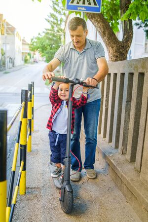 Small boy son child on the electric push kick scooter with his grandfather senior man helping him to learn to ride on the sidewalk